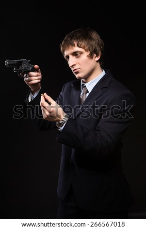 a man with a gun in studio. weapons, crime