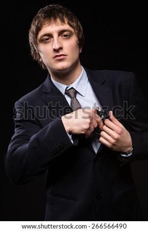 a man with a gun in studio. weapons, crime. man hides a gun - stock photo