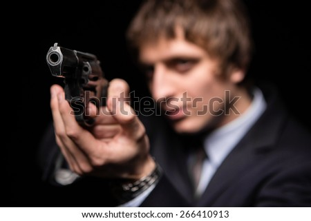 a man with a gun in studio. weapons, crime.  photo a young man drawing a gun in self defense studio shoot