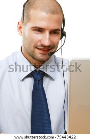 A man with a headset working on the laptop - stock photo