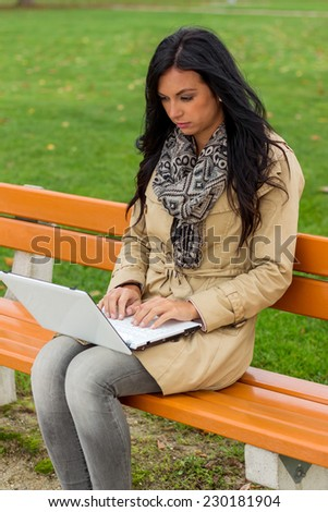 a man with a laptop sitting on a park bench - stock photo