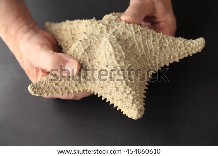 A man with a large seashell on a black background - stock photo