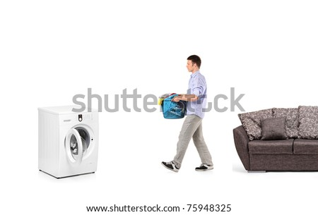 A man with a laundry basket going towards a washing machine isolated on white - stock photo