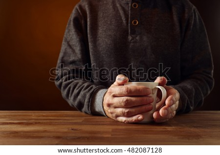 A man with a mug of hot coffee