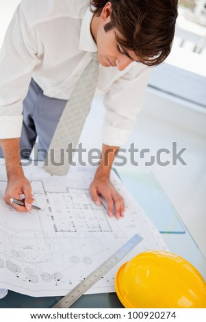 A man with a pen in hand is hard at work on some blueprints for work - stock photo
