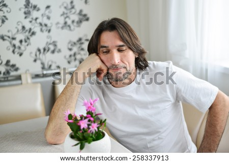 A man with a pink orchid in the room