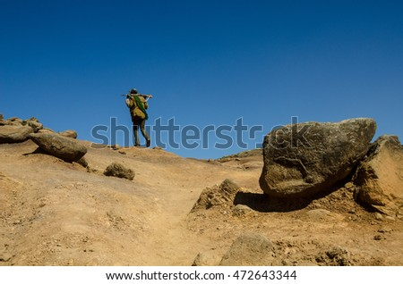 a man with a rifle over his neck is walking up a barren landscape into the deep blue sky.
