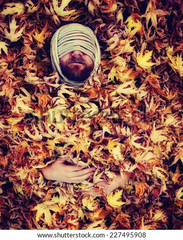a man with a rope wrapped around his head laying in a pile of leaves toned with a retro vintage instagram like filter effect  - stock photo