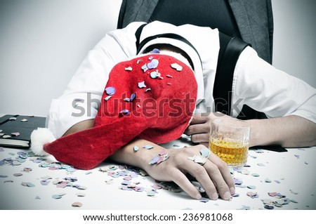 a man with a santa hat and covered with confetti sleeping in his desk after an office christmas party - stock photo