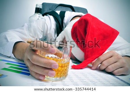 a man with a santa hat sleeping in his desk after an office christmas party - stock photo