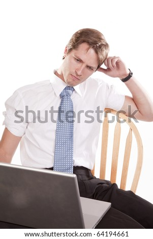 A man with a serious expression working on his computer.