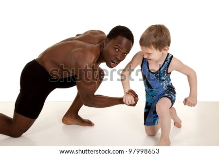 A man with a shocked expression on his face as the young boy is winning the arm wrestling.