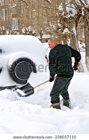 A man with a shovel digs up your car in the snow - stock photo