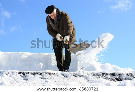 A man with a shovel removing snow from a roof - stock photo
