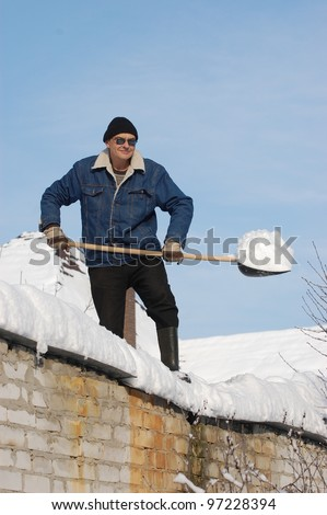 A man with a shovel removing snow from a roof . Near Kiev,Ukraine - stock photo