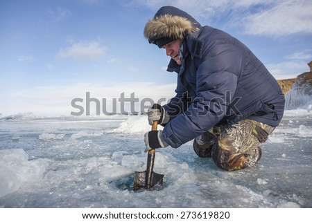 A man with a shovel splits the frozen ice in Lake Baikal - stock photo