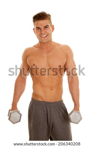 a man with a smile on his face holding onto weights.