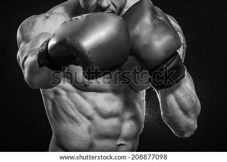 A man with a tattoo in red boxing gloves. Man boxing on black background. Boxer, boxing, tattoo, strength, punch, punching bag. - The concept of a healthy lifestyle.The idea for the film about boxing. - stock photo