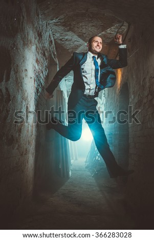 A man with a tie jumping in a long corridor