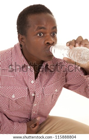 a man with a water bottle up to his lips because he is thirsty.