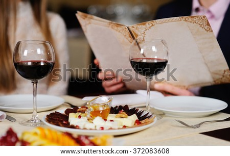a man with a woman in a restaurant menu background leaf table with food and wine - stock photo