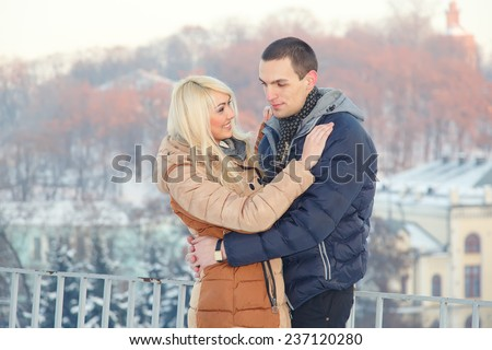 A man with a woman, winter love story. Young couple in love spending time outdoors. Girl blonde and brunette man. Trips winter day. Adventure tourism in the new town in the Christmas holidays. - stock photo