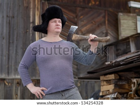 A man with an ax near the country house in winter