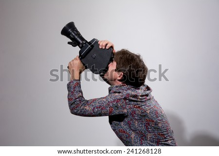 A man with an old movie camera on a gray background. Videographer to capture the camera sends up - stock photo