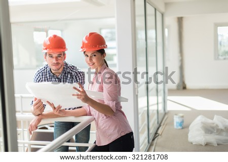 A man with beard and a woman are examining blueprints for a new project. They are standing in a glass open space, leaning against the guardrail. They are looking at camera and wearing orange hard hats - stock photo