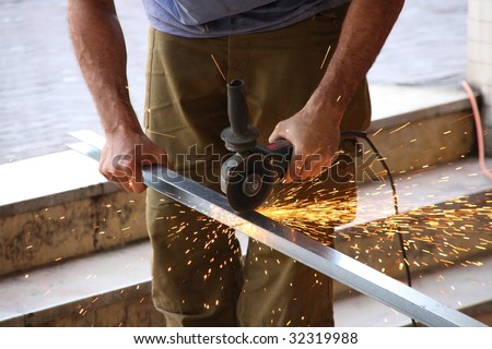 A man with circular saw in hands without gloves - stock photo