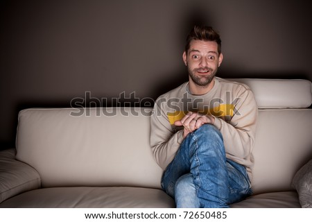 A man with crossed legs watching TV - stock photo