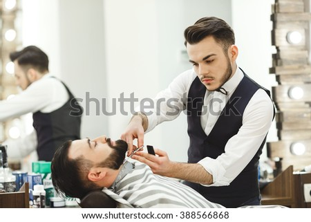 A man with dark hair wearing white shirt making beard form with scissors for man with black hair at barber shop, mirror at background, portrait.