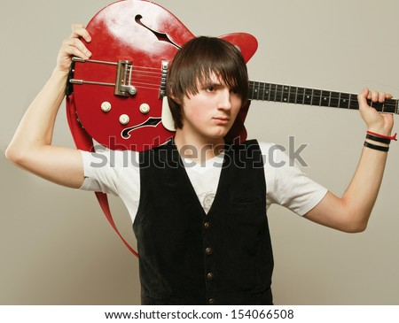 A man with guitar isolated on grey background - stock photo