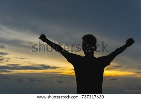 A man with hands raised in the sunset, worship. Cheering man open arms at the sunrise mountain peak. the concept of religion.