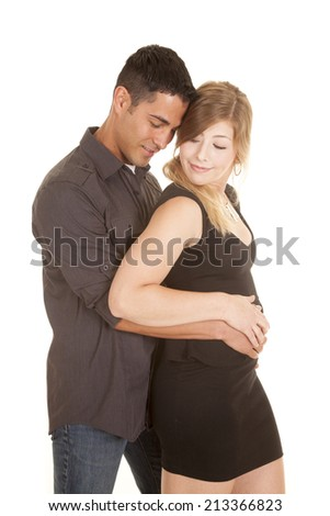 A man with his arms around his woman with a small smile on both of their lips.