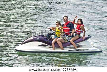 A man with his girls and dog waving from a jet ski.