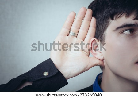 A man with his hand near his ear. Gesture can not hear without listening, talking louder. On a gray background