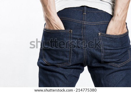 A man with his hands in jeans pockets - stock photo