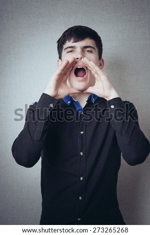 A man with his hands near his mouth. Gesture to call someone shout, speak loudly. On a gray background - stock photo
