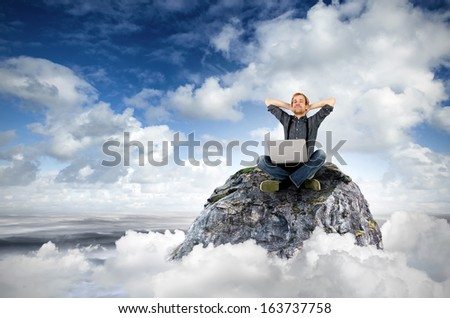 a man with laptop sits on a rock in the clouds