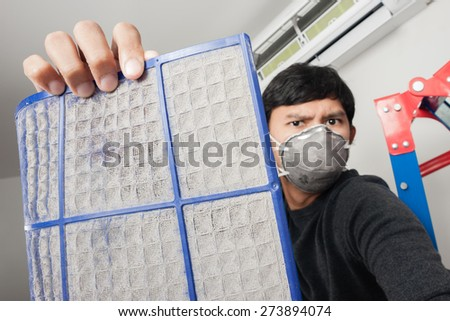 a man with mask showing dirty air filter before cleaning - stock photo