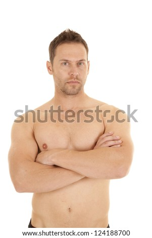 A man with no shirt on and arms folded with a serious expression on his face - stock photo
