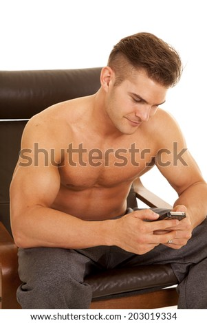a man with no shirt on sitting in his chair using his phone to text. - stock photo