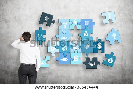 A man with one hand on head, the other in the pocket looking at a puzzle of different business components on a concrete wall, several parts missing. Concept of getting a full picture. - stock photo