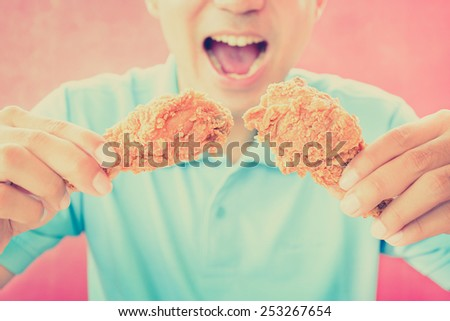 A man with opening mouth about to eat deep fried chicken legs or drumsticks -vintage (retro) style color effect - stock photo