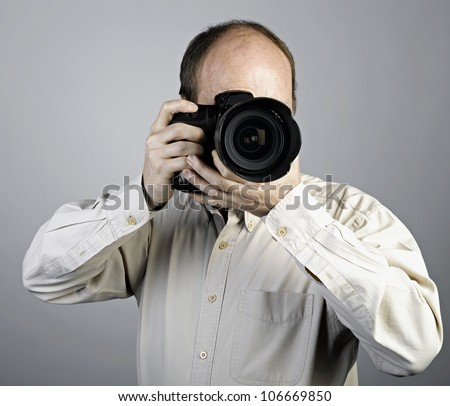 a man with photo camera on grey - stock photo