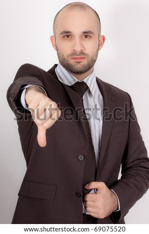 A man with suit and his thumb pointing down - stock photo