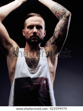 A man with tattooes on his arms. Silhouette of muscular body. caucasian brutal hipster guy with modern haircut, looking like criminal
