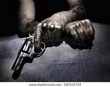 "A man with tattoos including ""love"" and ""hate"" holding a pistol./ Tattooed man with pistol - stock photo"