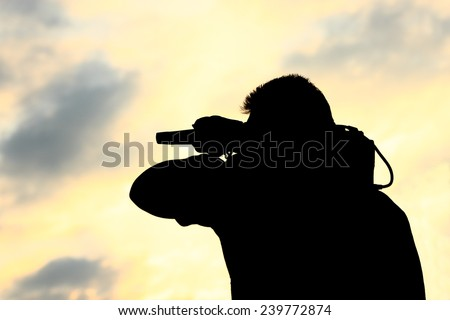 A man with TV camera on his shoulder silhouetted against sunset